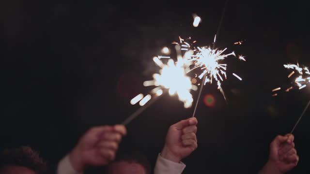 Hands hold lit sparklers up in the air at evening wedding reception.