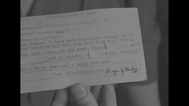 vs cu hands hold postcard sent by american pow roger heilig to his mother mrs oscar heilig from philippine military prison camp no 8 / 2shot man and... - postcard stock videos & royalty-free footage