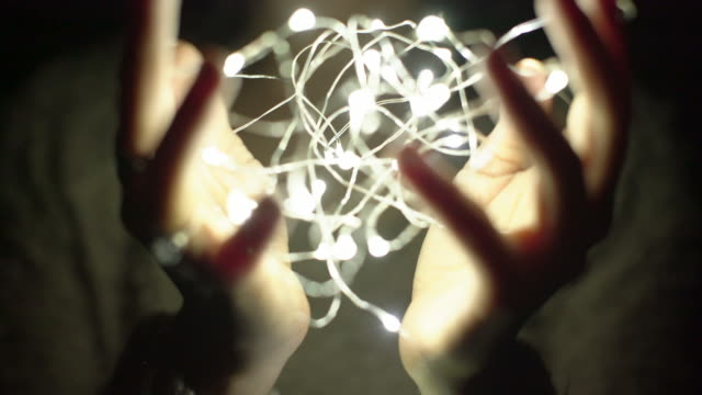 CU hands holding a ball of light at night