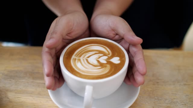 hands holding a cup of coffee , latte art , slow motion - coffee cup stock videos & royalty-free footage
