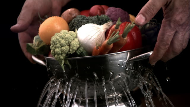 SLO MO, CU, Hands holding colander with vegetables