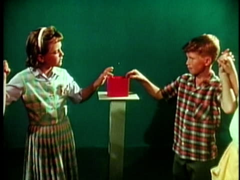 1961 cu zo hands holding electric meter with group of children demonstrating electrical current in background / united states / audio - touching stock videos & royalty-free footage