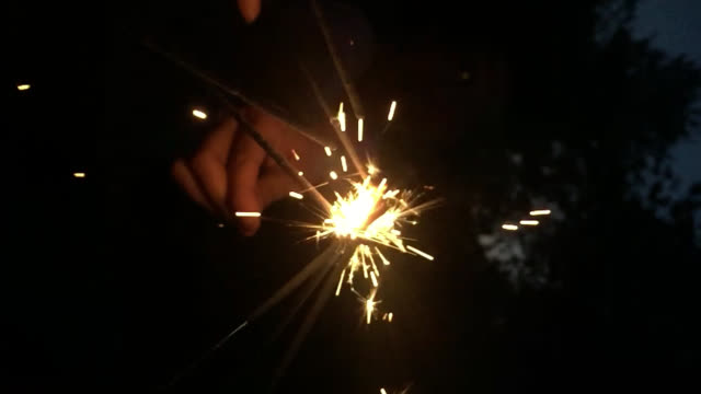 slo mo cu hands holding sparklers at night - 玩具花火点の映像素材/bロール