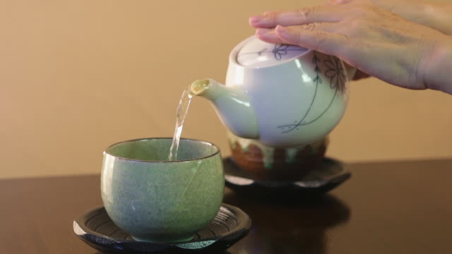 hands holding teapot and pouring tea into cup - 温かいお茶点の映像素材/bロール