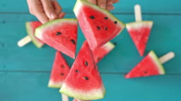 Hands holding watermelon slices high angle view