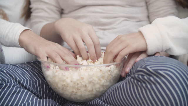4k: hands in bowl full of popcorn - slumber party stock videos & royalty-free footage