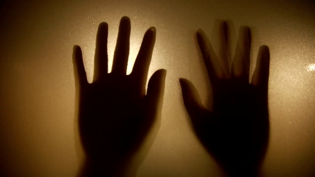 Hands in silhouette pressed against frosted glass