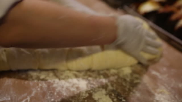 hands kneading dough in flour on wood surface - kneading stock videos & royalty-free footage
