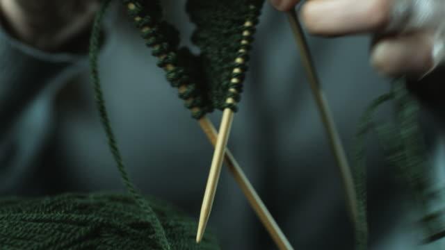 vídeos de stock e filmes b-roll de hands knitting with green yarn and wooden knitting needles - tricotar