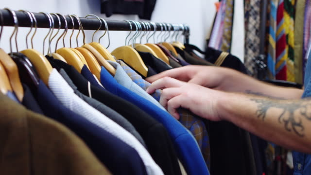 hands leafing through rack of second hand jackets - mercato delle pulci video stock e b–roll