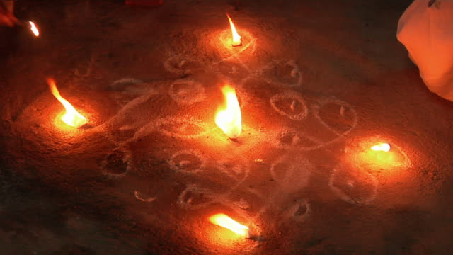 CU Hands lighting candles on dark floor, illuminating chalk drawings/ Hampi, Karnataka, India