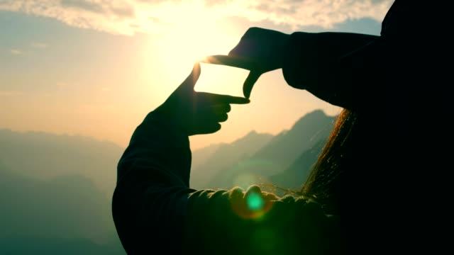 vídeos y material grabado en eventos de stock de manos haciendo un marco firme sobre puesta de sol - marco