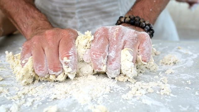 Hands making dough and rolling it out