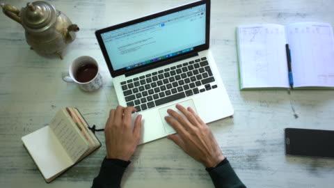 hands man using laptop and writing - skrivbord bildbanksvideor och videomaterial från bakom kulisserna