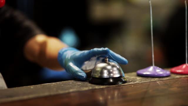 vídeos de stock e filmes b-roll de hands man with blue glove ringing bell at restaurant kitchen table. - sino