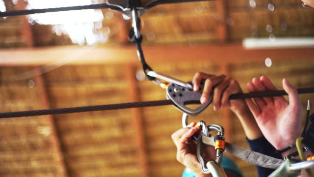 hand's men preparing the jungle zip line adventure equipment in the adventure park. - zip line stock videos & royalty-free footage