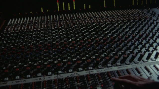 Hands mix sound on a sound board.
