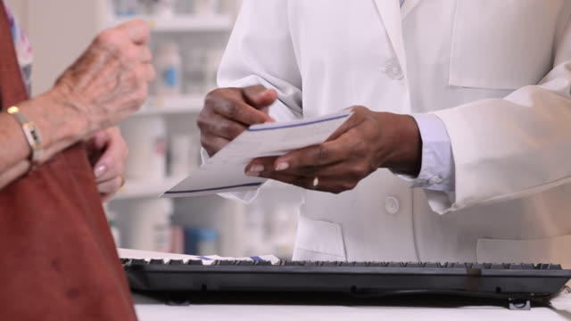 cu pan hands od pharmacist filling prescription and talking to customer at pharmacy counter / richmond, virginia, usa - prescription medicine stock-videos und b-roll-filmmaterial