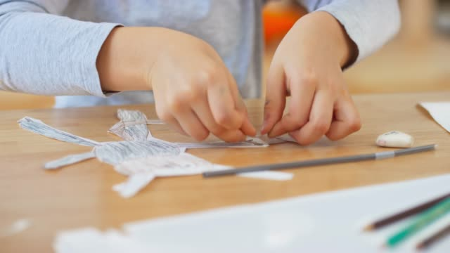 vídeos de stock e filmes b-roll de hands of a boy making a puppet out of paper - fantoche