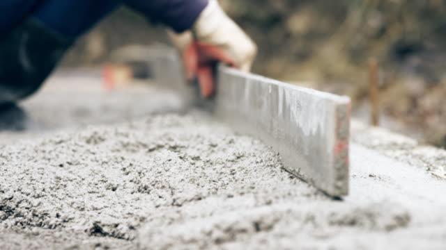 vídeos de stock e filmes b-roll de hands of a builder leveling the ground - ancinho equipamento de jardinagem
