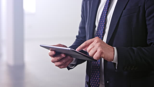 hands of a businessman typing on a digital tablet he is holding - usare un tablet video stock e b–roll