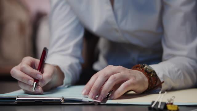 vídeos y material grabado en eventos de stock de manos de una mujer de negocios esperando nerviosamente en el escritorio - contrato