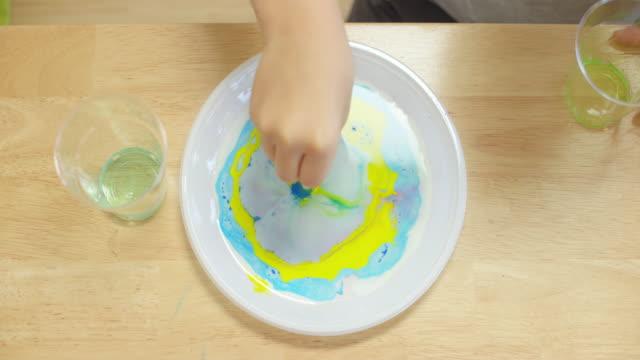 vídeos de stock, filmes e b-roll de as mãos de uma criança que fazem as cores na placa mudam usando um dab do algodão em uma experiência de leite em mudança - fazer