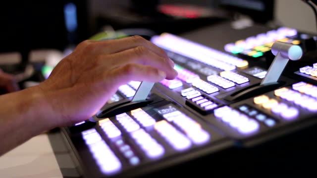 vídeos de stock, filmes e b-roll de mãos de um diretor de fotografia que trabalhou na mesa de mixagem de visão, mudar o painel de tv - canal