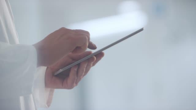 站在走廊上的醫生的手和滾動數位片 - 前景聚焦 個影片檔及 b 捲影像