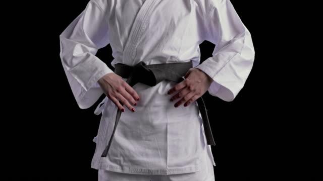 vídeos de stock, filmes e b-roll de slo mo zoom mãos de um karateist fêmea com pregos pintados que apertam sua correia preta - karate