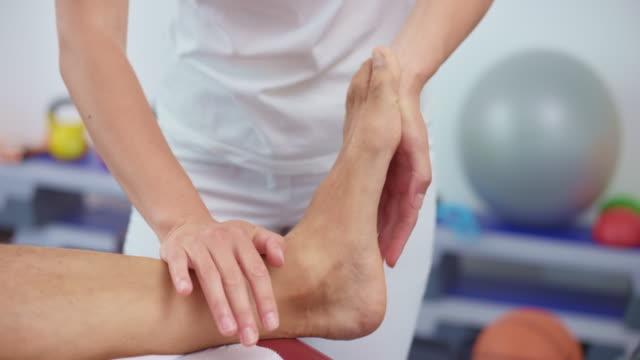 stockvideo's en b-roll-footage met slo mo handen van een vrouwelijke sporttherapeut die een problematische enkel masseert - massagetafel