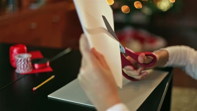 hands of a girl who is cutting a piece of paper - parte de una serie video stock e b–roll