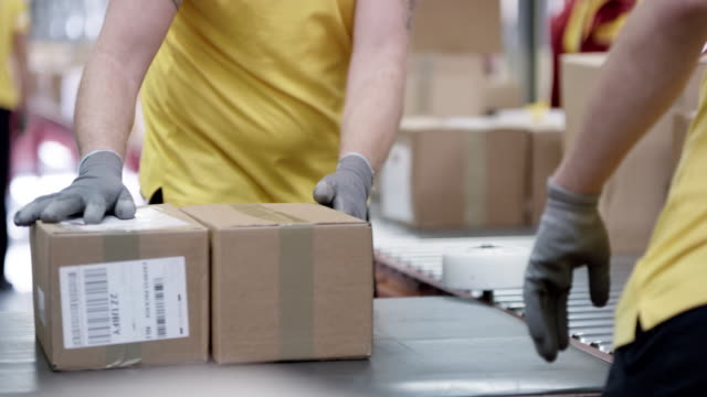 hands of a male and female postal worker sorting parcels on the conveyor belt - conveyor belt stock videos & royalty-free footage