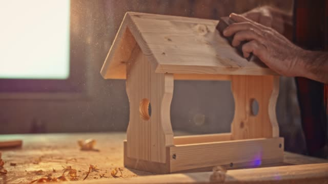 slo mo hands of a male carpenter finishing sanding the bird house in the sunny workshop - birdhouse stock videos & royalty-free footage