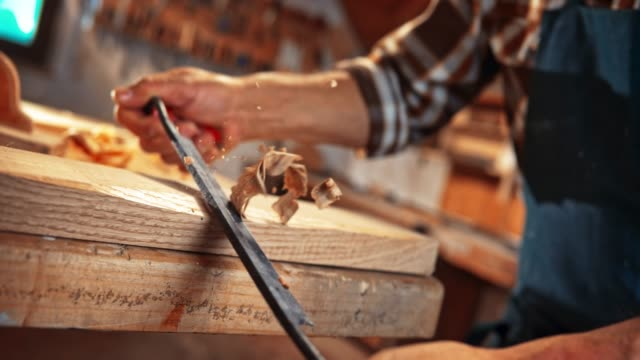 vídeos de stock e filmes b-roll de slo mo ds hands of a male carpenter holding a draw knife and trimming a plank - part of a series