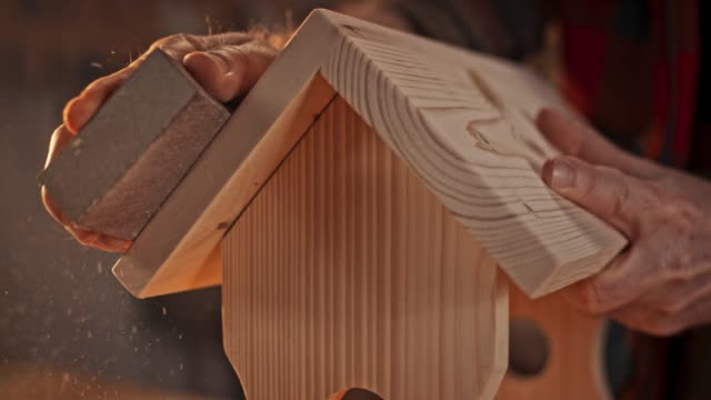 slo mo hands of a male carpenter sanding a bird house in the sunny workshop - carpenter stock videos & royalty-free footage