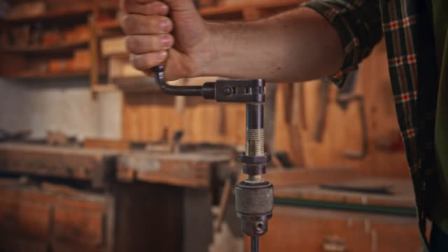 slo mo hands of a male carpenter using a hand drill to make a hole in the piece of wood - accuracy stock videos & royalty-free footage