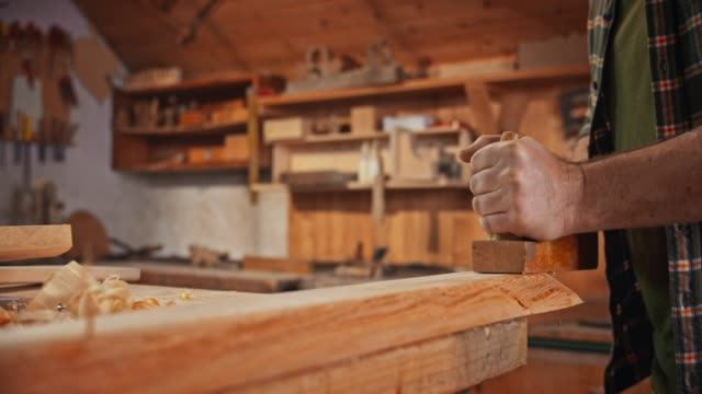 SLO MO Hands of a male carpenter using a plane to shape a piece of wood