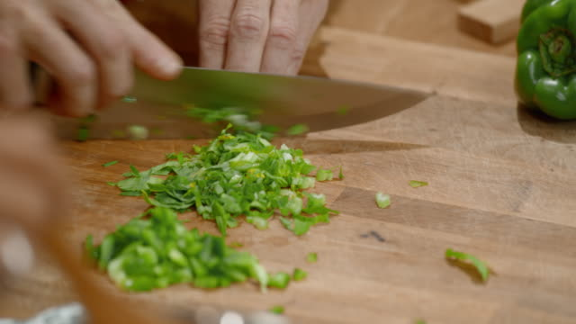 Hands of a male chef cutting fresh green herbs on a wooden board