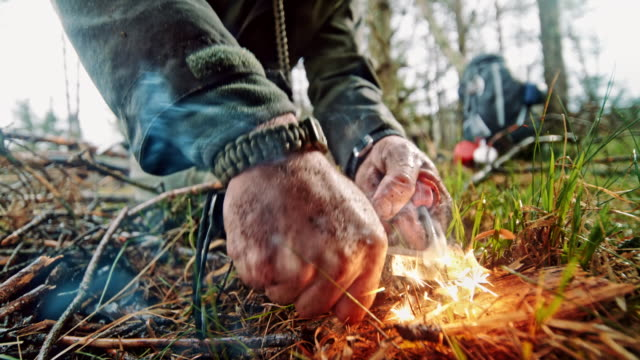 slo mo ld hands of a man starting a fire using a ferrocerium rod and a knife - survival stock videos & royalty-free footage