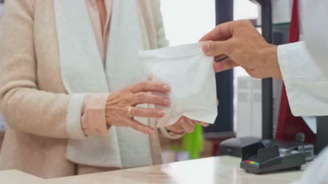 vídeos de stock e filmes b-roll de hands of a pharmacists placing the prescription medicine into a white bag and handing it to the customer - levantar