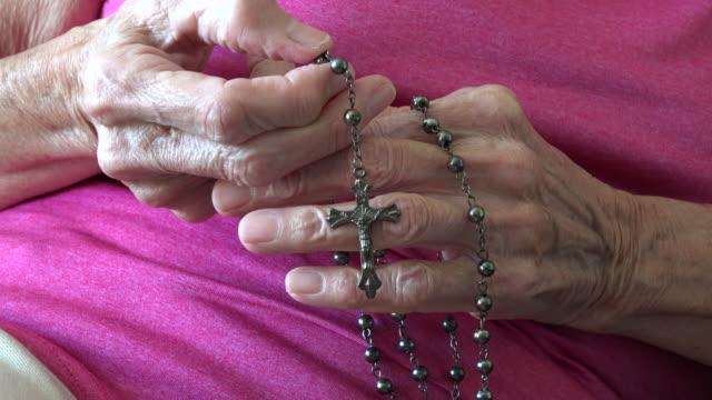 vídeos de stock e filmes b-roll de hands of a senior catholic woman saying her prayers with a rosary - catolicismo