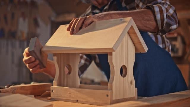 vídeos de stock, filmes e b-roll de mãos do mo de slo de um carpinteiro masculino sênior que termina a superfície de uma casa do pássaro que usa uma esponja de lixamento - oficina de trabalho