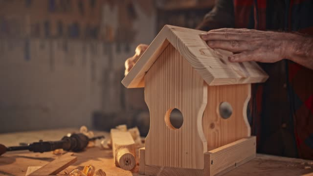 slo mo hands of a senior male carpenter using a sanding sponge to finish a bird house - carpenter stock videos & royalty-free footage