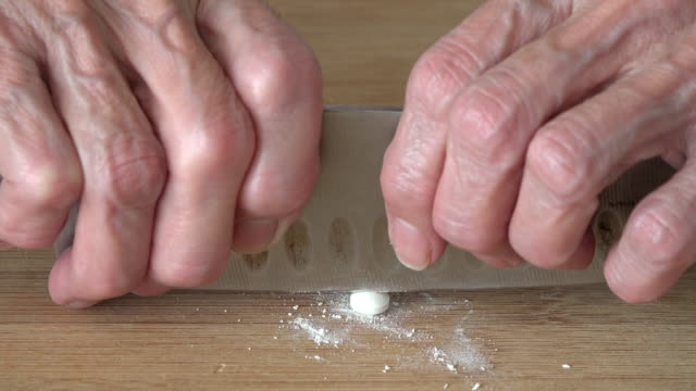 Hands of a senior woman cutting pills with a knife