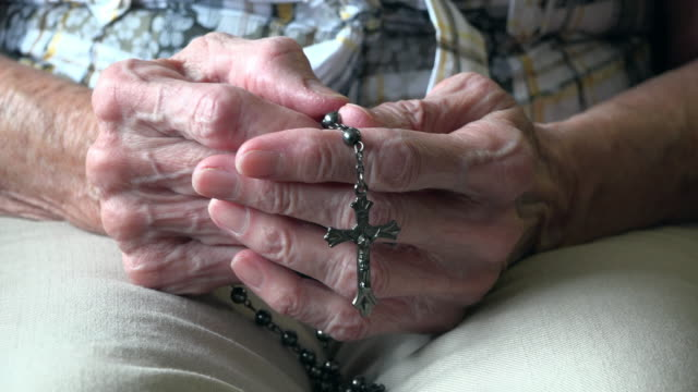 Hands of a senior woman holding a rosary while she prays