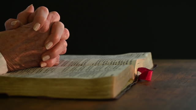 hands of a senior woman with bible praying at table - bible stock videos & royalty-free footage