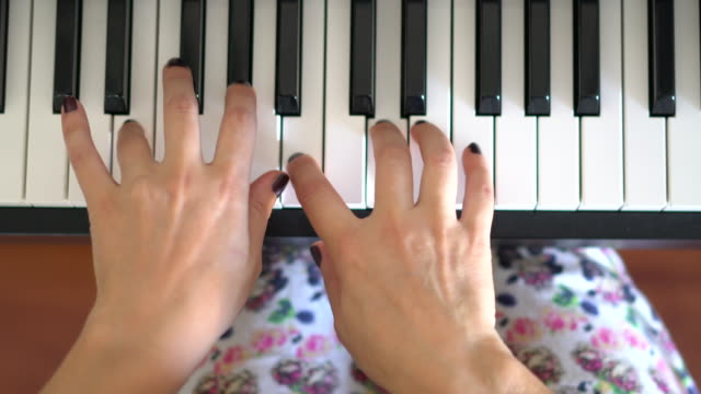 hands of a woman playing the piano from above - piano key stock videos & royalty-free footage