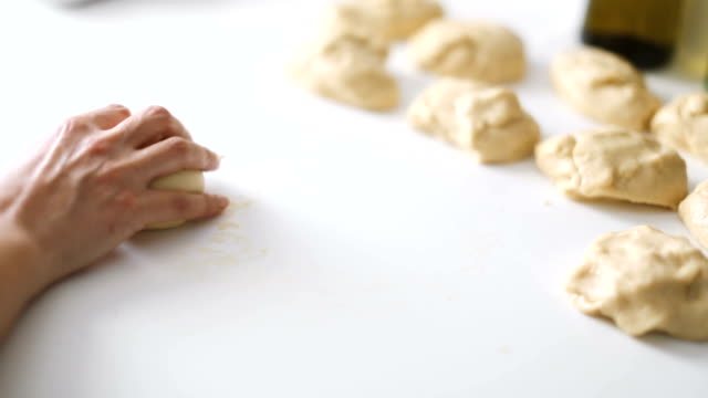 hands of a woman rolling and preparing the dough to make homemade pastry - tipo di panino video stock e b–roll
