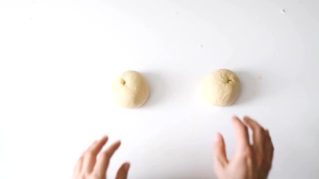 手作りのペストリーを作るために生地をローリングし、準備する女性の手 - バンズ点の映像素材/bロール